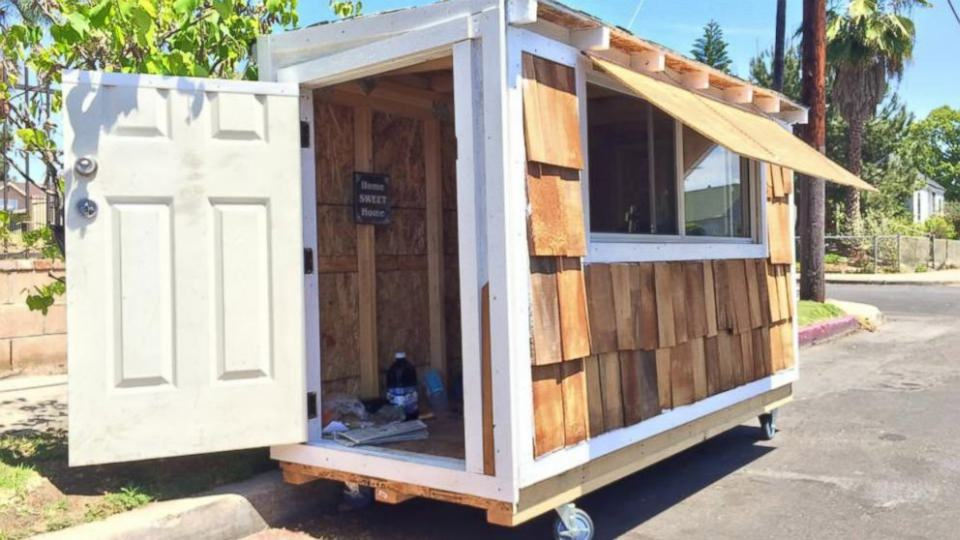 Tiny House features  door with lock and sliding windows.