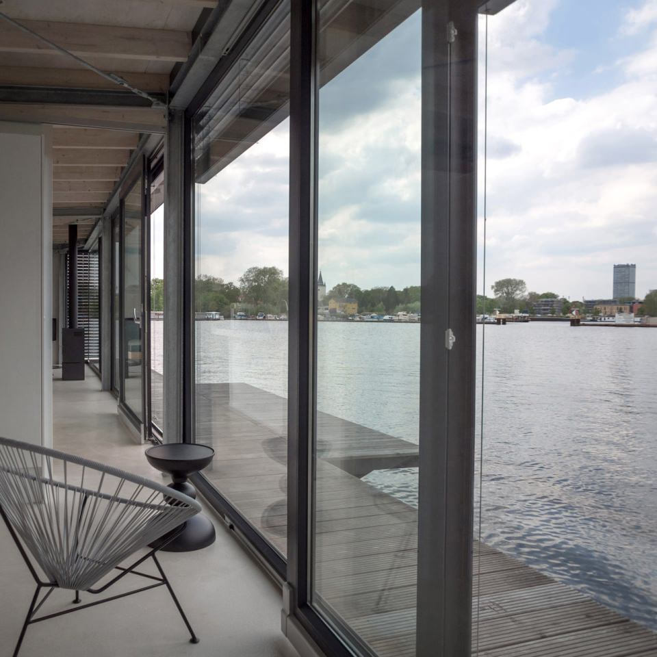 The front structure of the houseboat is built with windows and opens to the bay