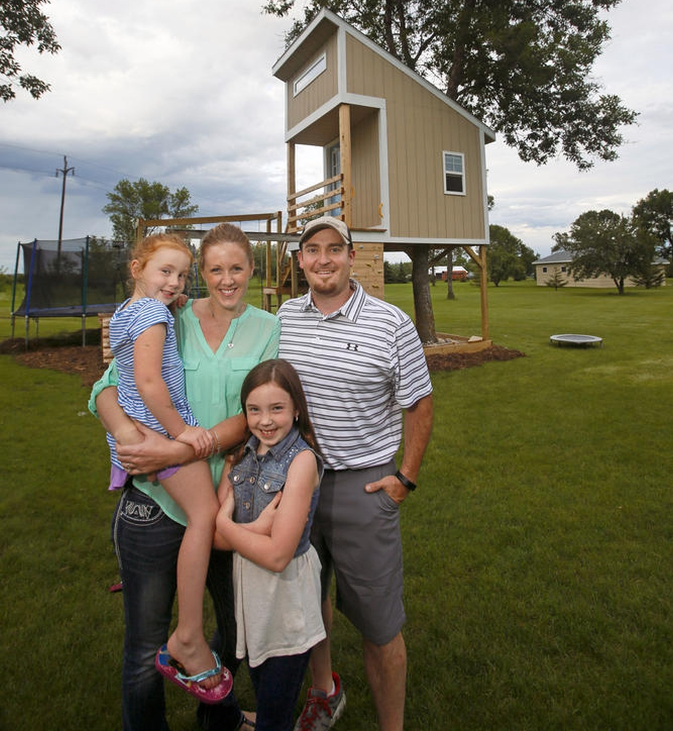 The complete family outside their newly built treehouse