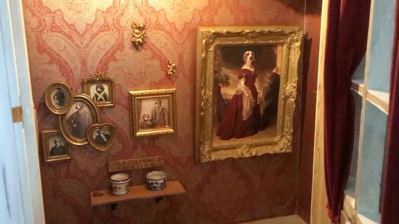 Dog house with portraits of Jessie hung on the walls
