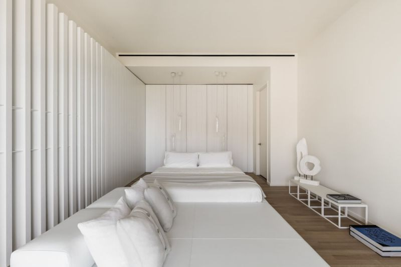 Two sides of bedroom made with vertical white stained oak panels