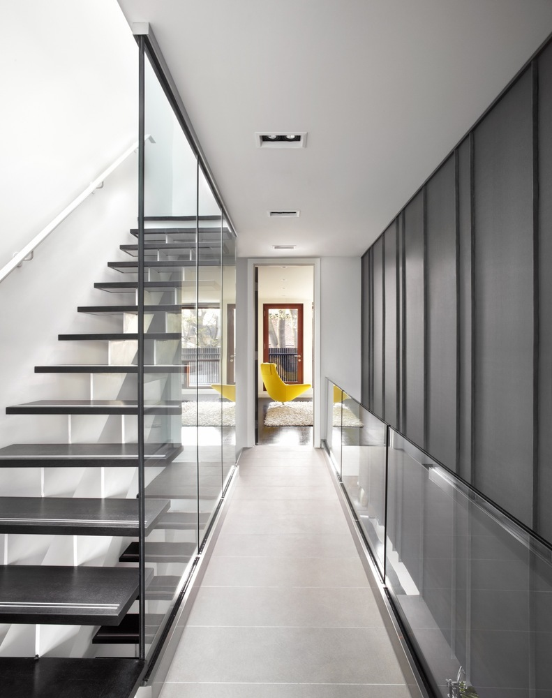 Elegant staircase by the side glass railing and wall