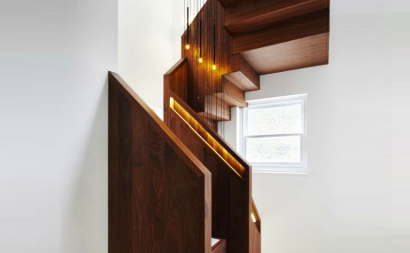 Wooden staircase with hidden handrail lighting